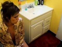 Brunette with a pierced belly takes a pee