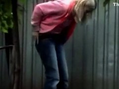 Blonde girl in tight jeans pants peeing outdoors