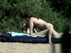 Naturist couple spied in the river shore having sex